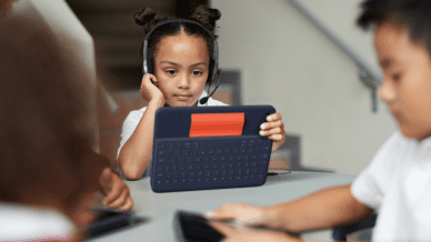 young girl sitting at table at school wearing a headset and holding a tablet, as example of tech tool ideas