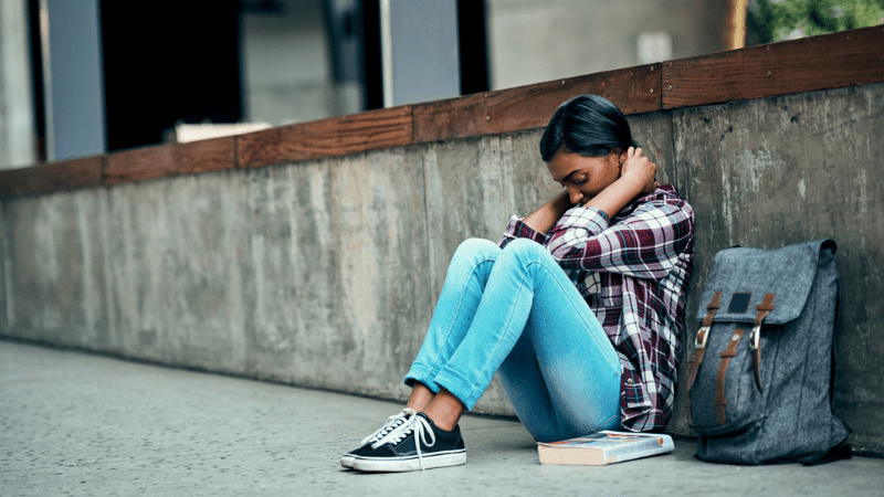 Adolescent girl who needs youth suicide prevention sitting outside school with head down